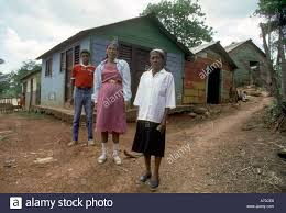 one storey house dominican republic family outside their wooden one storey house in