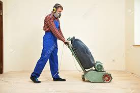 carpenter doing parquet wood floor polishing maintenance work