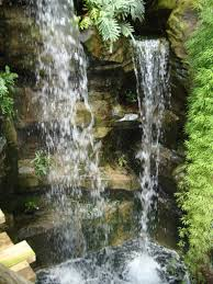 amazing natural waterfall with green plants and rustic stone for
