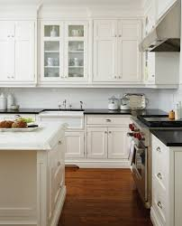 kitchens with different colored islands kitchen with glass cabinets and black leathered perimeter counter