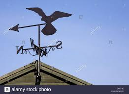 Airplane Weathervane Falcon Weather Vane On A Garden Shed Against A Blue Sky Stock
