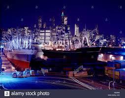 new york skyline and brooklyn shipping docks at night stock photo