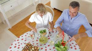 couple seated around dining table serving one another before woman
