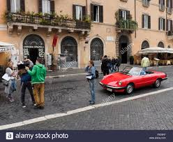 film crew and male models in a classic alfa romeo sportscar on