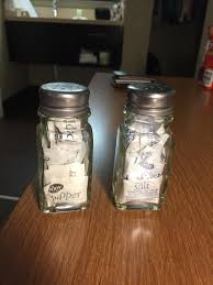 these salt and pepper shakers filled with salt and pepper packets