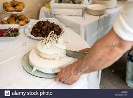 groom at marriage cutting the wedding cake together stock photo