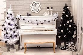 black and white christmas tree near white piano holiday photos