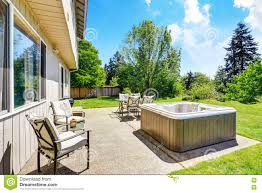 backyard concrete floor patio area with tub well kept lawn