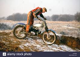 snow motocross bike old man on trials motor bike in country after fall of snow stock