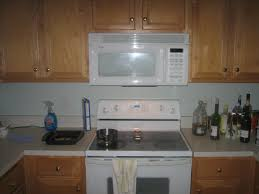 white microve shelf above stove under oak kitchen cabinet with
