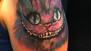 cheshire cat tattoo on shoulder by junba nadal