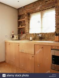 stone sink below window in exposed brick wall in modern country