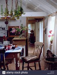 White Country Kitchen by Old Pine Chair And Table In White Country Kitchen With Bunches Of