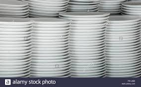 Wire Rack Shelf Stacks Of Many White Plates On A Wire Rack Shelf In A Commercial