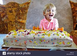 little boy with giant birthday cake stock photo royalty free