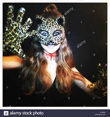 a 13 year old wearing a cat mask poses for a picture on stock