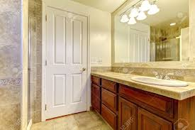 bathroom with stone tiles and glass shower with wood cabinets