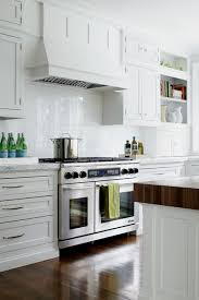 beautiful white kitchen with a marble backsplash featuring the