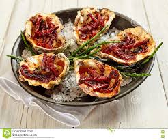 plate of oysters kilpatrick on painted wood table stock image
