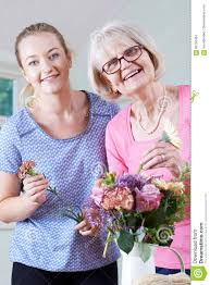 senior woman with teacher in flower arranging class stock photo