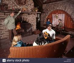 1960s three couples men women in ski lodge by stone fireplace fire