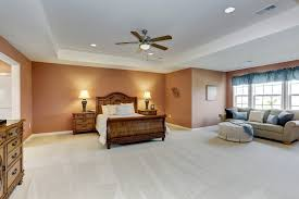 lovely orange bedroom with tray ceiling and a cozy sitting area