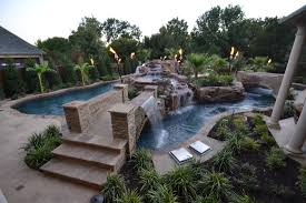 large contemporary backyard lazy river pool with stone coping deck and tiles plus brick bridge with waterfall surrounded by garden with various plants ideas