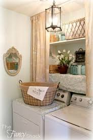 laundry room with gray green cabinets paired with white quartz