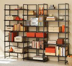 black metal bookshelves with many racks connected by beige wall of