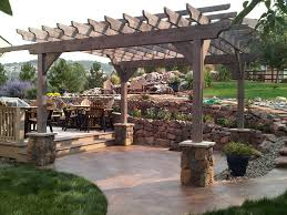 rough sawn timber pergola stone piers rock retaining wall