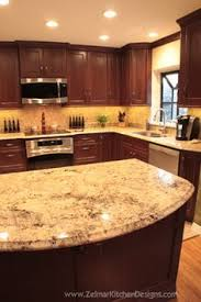 cherry kitchen cabinets with gray wall and quartz countertops
