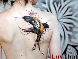 watercolor flying bird tattoo on girls back