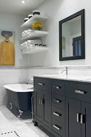 bathroom with clawfoot tub and towel storage shelves towel
