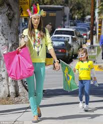 alessandra ambrosio wears face paint and feathered headdress with