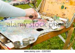 painter knife mixing oil colors on a wooden palette stock photo