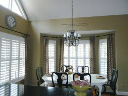 bay window with plantation shutters and curtains for the home