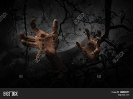spooky background halloween zombie hand rising out from old fence over dead tree crow moon and