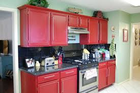 simple small metal gasstove between big red kitchen cabinets close
