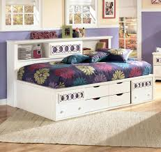 white wooden daybed with storage drawer and dark purple bed sheet