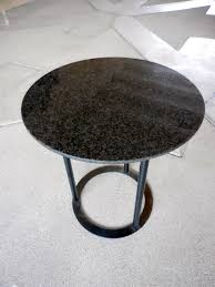 round glass side table on curving black acrylic pedestal base of