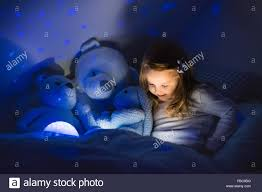 little reading a book in bed dark bedroom with night light