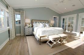 steely light blue bedroom walls wide plank rustic wood floors patterned curtains lots of light vaulted planked ceiling wood floor pattern