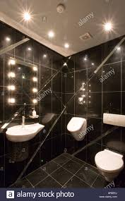 modern black tiled toilet with angled mirrors and sunken halogen