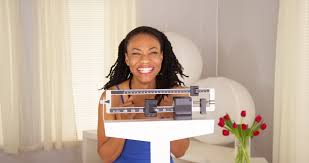 black woman excited about weight loss on scale stock footage video