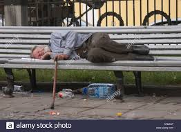 homeless old man sleeping on the bench in the street of moscow