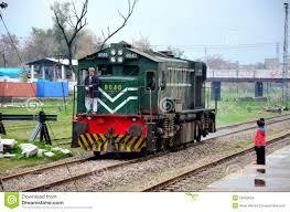 pakistan railways locomotive engine passes as small child watches