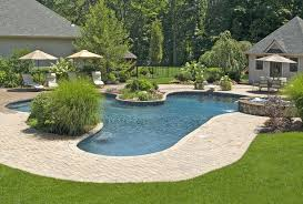 backyard pergola in front of swimming pool with brick waterfall