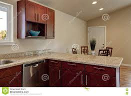 view of burgundy kitchen cabinets with granite counter top stock