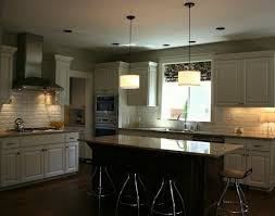 modern drum shape pendant lamps over granite top kitchen island of