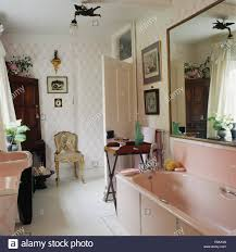 large mirror above pale pink bath in country bathroom with stock